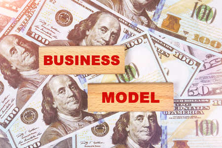 Business concept. Against the background of dollar bills, the text is written on wooden blocks - business model