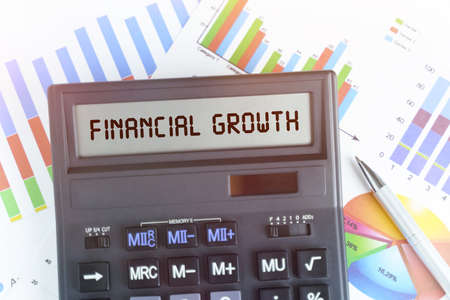 The concept of business and finance. On the table are financial charts and a calculator, on the electronic board of which is written the text - FINANCIAL GROWTH