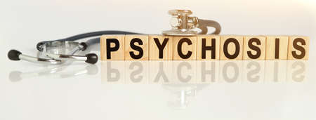 PSYCHOSIS the word on wooden cubes, cubes stand on a reflective white surface, on cubes - a stethoscope. Medicine concept