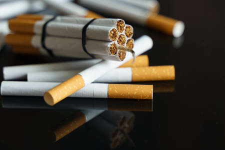The concept of medicine is the fight against smoking. Cigarettes, in the form of sticks of dynamite, lie among the scattered cigarettes on a black reflective surface.