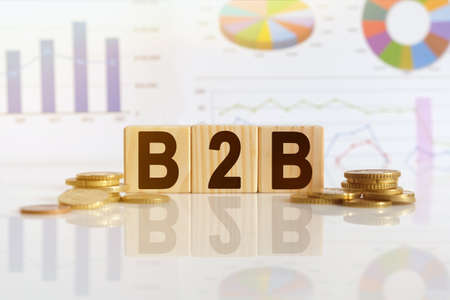 Business to Business. B2B the word on wooden cubes, cubes stand on a reflective surface, in the background is a business diagram. Business and finance concept
