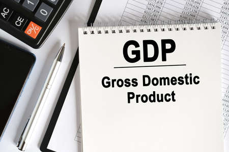 On the table lies a smartphone, a calculator and a notebook with the inscription- GDP. Gross Domestic Product. Business concept