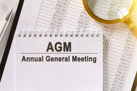 On the table are financial reports, a pen, a magnifying glass and a notebook with the inscription - AGM. Annual General Meeting. Business and finance concept. Stok Fotoğraf - 151336627