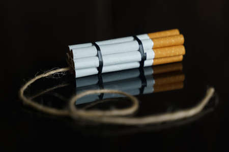 The concept of medicine is the fight against smoking. Cigarettes are twisted into a dynamite checker with a filament on a black reflective surface. Imagens