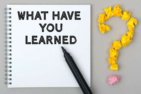 Hand with marker writing: What Have You Learned. Notepad and question mark.