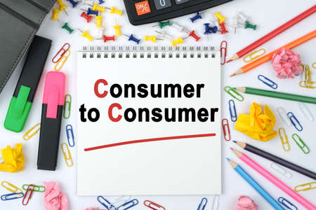 Business concept. On the table is a calculator, diary, markers, pencils and a notebook with the inscription - Consumer to Consumer