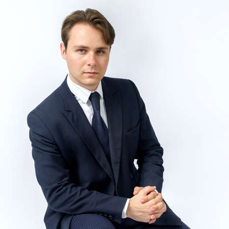 A portrait of a businessman in a blue suit who is clutching his hands. White background. Business and finance concept