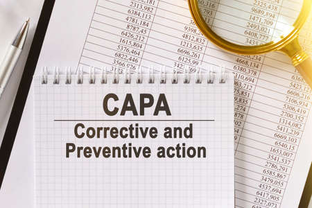On the table are financial reports, a pen, a magnifying glass and a notebook with the inscription - CAPA. Corrective and Preventive action. Business and finance concept.