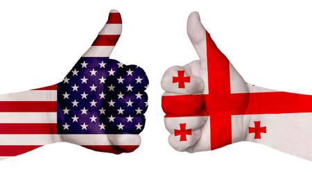 The concept of strengthening the relationship of nations. Two hands are painted with flags of different countries, with a thumb raised up. Georgia and the USA