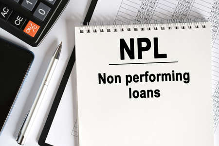 On the table lies a smartphone, a calculator and a notebook with the inscription- NPL. Non performing loans. Business concept