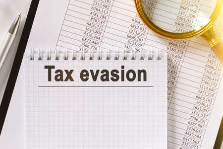 On the table are financial reports, a pen, a magnifying glass and a notebook with the inscription - Tax evasion. Business and finance concept.