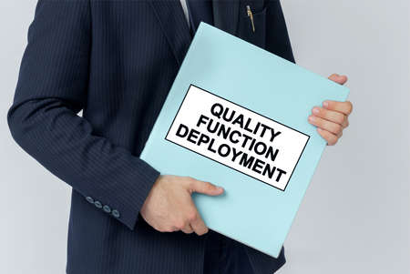 Business concept. A businessman holds a folder with documents, the text on the folder is - QUALITY FUNCTION DEPLOYMENT