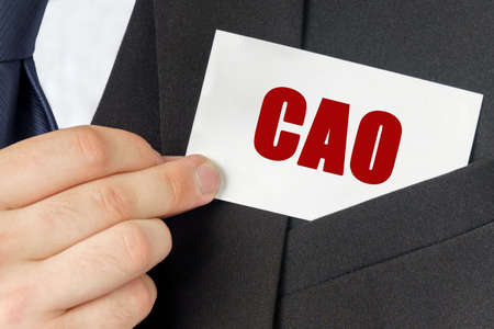 Business concept. Businessman holds a card with the text - CAO 스톡 콘텐츠