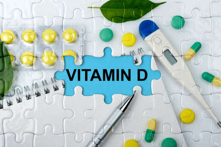 Double exposure. Puzzles with the image of tablets, a notebook, a thermometer and a pen with the inscription -VITAMIN D. The concept of medicine.