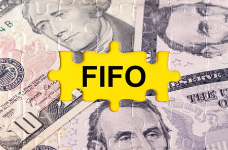 Business concept. Puzzle with the image of dollars in the center of the inscription -FIFO