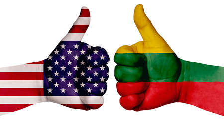 The concept of strengthening the relationship of nations. Two hands are painted with flags of different countries, with a thumb raised up. Lithuania and the USA