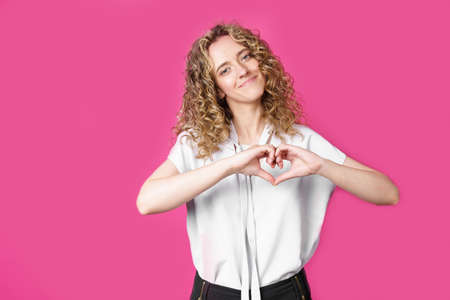 Portrait of a beautiful woman who shows a heart gesture on her chest, passionately, expresses love for a loved one. Isolated pink background. Stock fotó