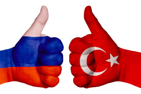 The concept of strengthening the relationship of nations. Two hands are painted with flags of different countries, with a thumb raised up. Russia and Turkey