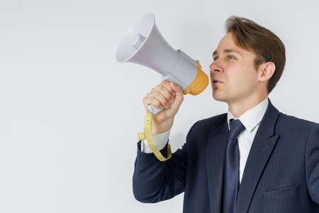 A businessman speaks into a loudspeaker. White background. Business and finance concept