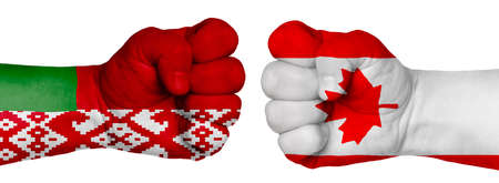 The concept of the struggle of peoples. Two hands are clenched into fists and are located opposite each other. Hands painted in the colors of the flags of the countries. Canada vs Belarus