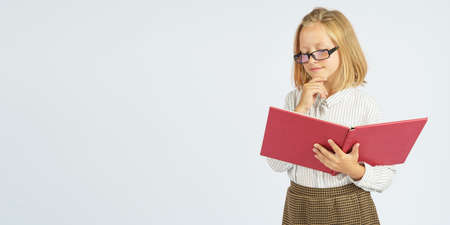A teenager girl in glasses, holds her chin with her hand and reads a book. Isolated background. Education concept.