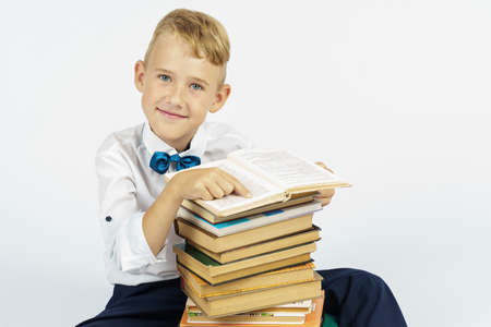 A schoolboy is sitting near a stack of books and smiling while looking at the camera. Isolated background. Education concept Foto de archivo