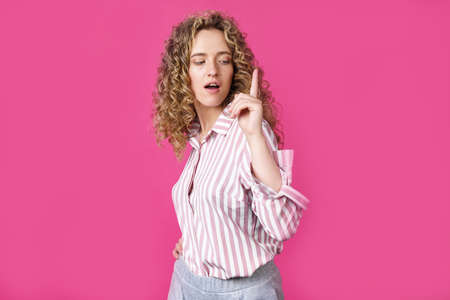 Young beautiful woman, amazed and surprised, looking up and pointing with fingers and raised hands. Isolated on pink background.