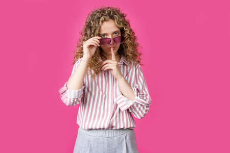 The young woman holds onto her glasses and makes a gesture with her hands - quietly. Secret, secret, isolated on pink background Stock fotó