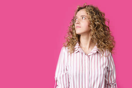 Young beautiful woman thinking looking to the side at blank copy space. Isolated pink background