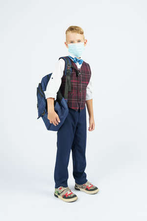 A schoolboy with a medical mask on his face holds a school backpack, stands sideways, looks at the camera. Education concept