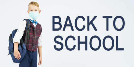 Education concept. A schoolboy with a medical mask on his face is holding a school backpack, next to it is written the text - BACK TO SCHOOL