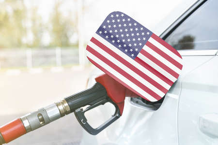 Energy and economy concept. Flag of USA on the car's fuel filler flap with gas pump nozzle in the tank.