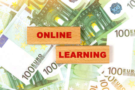 Business concept. Against the background of euro bills, the text is written on wooden blocks - online learning Stock fotó