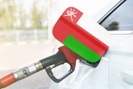 Energy and economy concept. Flag of Oman on the car's fuel filler flap with gas pump nozzle in the tank.