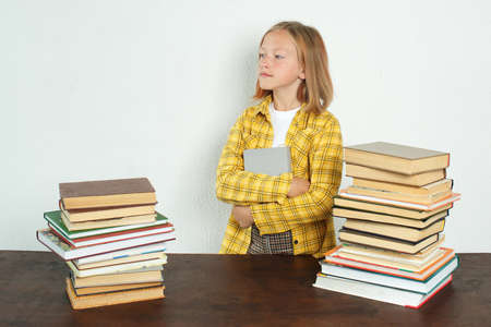 Education concept. A teenage girl stands near a table with books, holding a book in her hands.