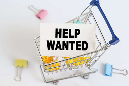 Business concept. In the shopping cart, the text is written on the card - HELP WANTED. Stock fotó