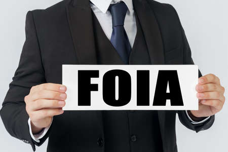 Business and finance concept. A businessman holds a sign in his hands which says FOIA