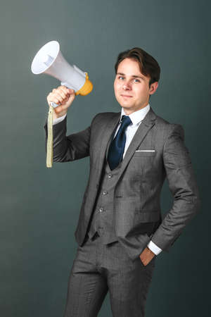 Business and finance concept. Portrait of a businessman who holds a megaphone in his hands. Light background