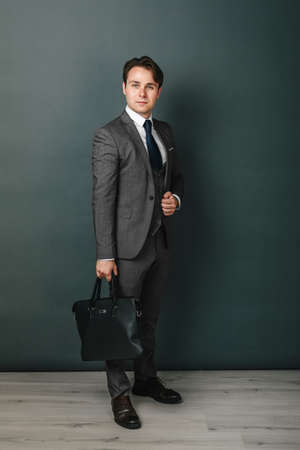 Business and finance concept. Portrait of a businessman who is holding a briefcase. Light background