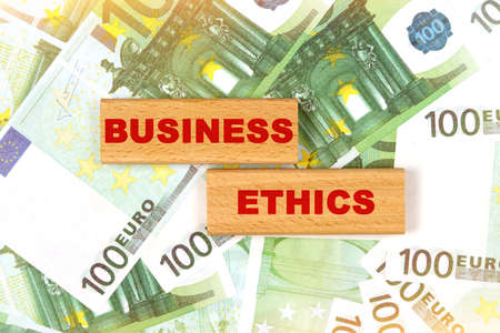 Business concept. Against the background of euro bills, the text is written on wooden blocks - business ethics