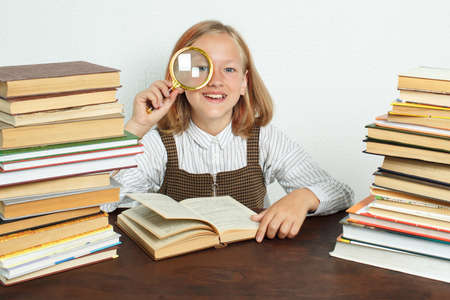 Education concept. A teenage girl sits among the books and looks through a magnifying glass. Stock Photo