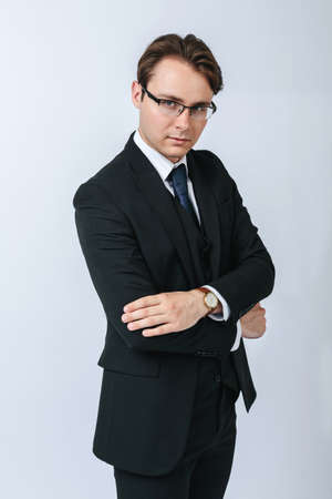 Business and finance concept. Portrait of a businessman in a black suit with glasses. Light background