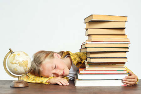 Education concept. The student fell asleep while doing her homework. Near books and a globe