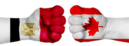 The concept of the struggle of peoples. Two hands are clenched into fists and are located opposite each other. Hands painted in the colors of the flags of the countries. Canada vs Egypt