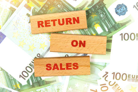 Business concept. Against the background of euro bills, the text is written on wooden blocks - return on sales