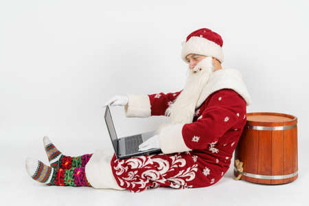 Christmas and New Years concept. Santa Claus is sitting on the floor and working at a laptop. Isolated background. Archivio Fotografico