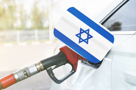 Energy and economy concept. Flag of Israel on the car's fuel filler flap with gas pump nozzle in the tank.
