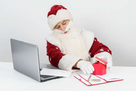 Christmas and New Year concept. Santa Claus is sitting at his desk and wrapping a gift.