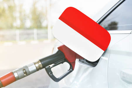 Energy and economy concept. Flag of Indonesia on the car's fuel filler flap with gas pump nozzle in the tank.
