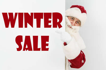 New Year and Christmas concept. Santa Claus points his fingers at the board with the text - WINTER SALE